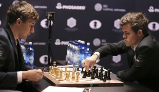Chess world champion Magnus Carlsen, right, of Norway, makes a move as challenger Sergey Karjakin, of Russia, watches during the fourth round of the World Chess Championship in New York, Tuesday, Nov. 15, 2016. (AP Photo/Seth Wenig)