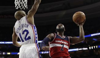 Washington Wizards' John Wall, right, goes up for a shot against Philadelphia 76ers' Gerald Henderson during the second half of an NBA basketball game, Wednesday, Nov. 16, 2016, in Philadelphia. Philadelphia won 109-102. (AP Photo/Matt Slocum)