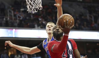 Washington Wizards guard John Wall (2) shoots a reverse layup past New York Knicks forward Kristaps Porzingis (6) during the second half of an NBA basketball game in Washington, Thursday, Nov. 17, 2016. The Wizards won 119-112. (AP Photo/Manuel Balce Ceneta)