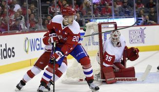 Washington Capitals center Lars Eller (20), of Denmark, works the puck as Detroit Red Wings goalie Jimmy Howard (35) watches during the first period of an NHL hockey game, Friday, Nov. 18, 2016, in Washington. (AP Photo/Nick Wass)