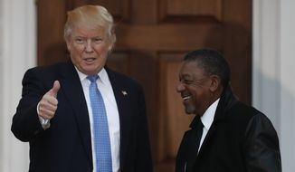 President-elect Donald Trump calls out to media as he poses for photos with BET founder Robert Johnson at the Trump National Golf Club Bedminster clubhouse, Sunday, Nov. 20, 2016, in Bedminster, N.J.. (AP Photo/Carolyn Kaster)