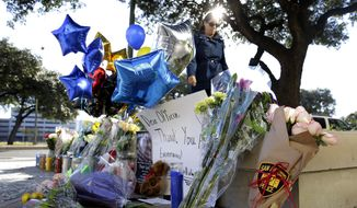 A woman leaves flowers at a makeshift memorial for slain San Antonio police officer Benjamin Marconi, 50, a 20-year veteran of the force, Monday in San Antonio. Marconi was fatally shot during a traffic stop near police headquarters Sunday. (Associated Press)