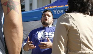 Marcus Ruiz Evans (center) of The Yes California Independence Campaign, talks to passersby about California succeeding from the United States and becoming its own nation in Sacramento on Nov. 9, 2016. A group calling for California to secede from the United States submitted a proposed petition Monday, Nov. 21, 2016, seeking a ballot measure that would strip the state constitution of language that says California is an inseparable part of the nation. The Yes California Independence Campaign hopes to put a question on the November 2018 ballot authorizing a vote on independence in spring 2019. (Associated Press) **FILE**
