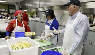 Vice President-elect Mike Pence and his wife, Karen, talk with Second Helpings' Chef Liz Gimenez as they slice vegetables for Thanksgiving meals, Wednesday, Nov. 23, 2016, in Indianapolis. (AP Photo/Darron Cummings)