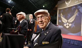 """In this April 18, 2015, file photo, two members of the Doolittle Tokyo Raiders, retired Lt. Col. Richard """"Dick"""" Cole, seated foreground, and retired Staff Sgt. David Thatcher, seated background left, pose for photos after the presentation of a Congressional Gold Medal honoring the Doolittle Tokyo Raiders at the National Museum of the U.S. Air Force at Wright-Patterson Air Force Base in Dayton, Ohio. The National Museum of the U.S. Air Force plans to mark the 75th anniversary of the Doolittle Tokyo Raiders attack on Japan on April 17 and 18, 2017, and Cole, the only one of the 80 airmen still alive, expects to attend and help pay tribute to Thatcher, who died June 22, 2016, in Montana. (AP Photo/Gary Landers, File)"""