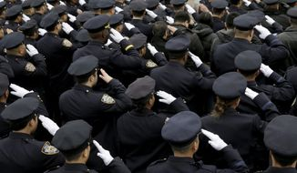 NYPD officers salute during the funeral of Officer Wenjian Liu in the Brooklyn borough of New York on Jan. 4, 2015. Liu and his partner, officer Rafael Ramos, were killed Dec. 20, 2014, as they sat in their patrol car on a Brooklyn street. The shooter, Ismaaiyl Brinsley, later killed himself. (Associated Press)