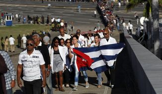 Mourners hold a Cuban flag as they line up at Revolution Plaza, the site of two days of tributes to the late Fidel Castro, in Havana, Cuba, Monday, Nov. 28, 2016. Thousands of Cubans began lining up early for the start of week-long services bidding farewell to the man who ruled the country for nearly half a century. (AP Photo/Dario Lopez-Mills)