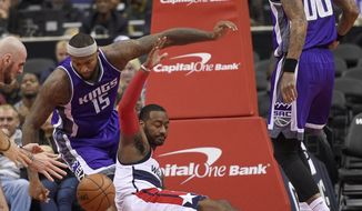 Washington Wizards guard John Wall, right, loses the ball against Sacramento Kings center DeMarcus Cousins (15) during the first half of an NBA basketball game, Monday, Nov. 28, 2016, in Washington. (AP Photo/Nick Wass)