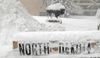 A sculpture of a Bison on the state Capitol grounds in Bismarck was covered in snow Tuesday, the second day of a winter storm in central North Dakota. (Associated Press)