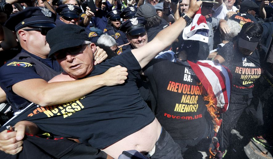 """FILE - In this July 20, 2016 file photo, a law enforcement officer takes Gregory """"Joey"""" Johnson into custody after he started to burn an American flag in Cleveland, during the third day of the Republican convention. President-elect Donald Trump said Tuesday that anyone who burns an American flag should face unspecified """"consequences,"""" such as jail or a loss of citizenship _ a move that was ruled out by the Supreme Court nearly three decades ago.  (AP Photo/John Minchillo)"""