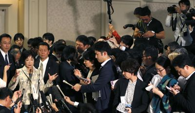 Tokyo Gov. Yuriko Koike, left, is surrounded by the media after IOC debriefing in Tokyo Tuesday, Nov. 29, 2016. Top international and Japanese Olympic officials discussing three expensive venues and cost cutting measures have agreed to keep two - rowing and swimming venues - at their planned sites in Tokyo while making further cost reduction effort, while putting off a decision on a volleyball arena until Christmas. Koike accepted the plan in the meeting that the rowing and swim sites will stay, but with further cost-cutting effort. (AP Photo/Shuji Kajiyama)