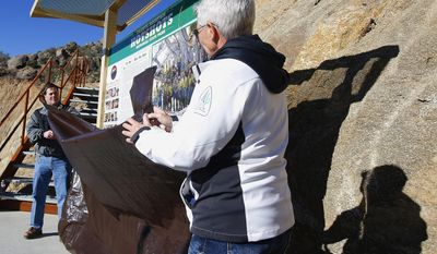 Arizona Republican Gov. Doug Ducey, left, and Director of the Arizona State Parks Sue Black, right, unveil a trailhead sign during a dedication ceremony for the new Granite Mountain Hotshots Memorial State Park as a tribute to the 19 firefighters killed during a 2013 wildfire Tuesday, Nov. 29, 2016, in Yarnell, Ariz.  Ducey said the 3-mile trail and memorial would serve as a lasting tribute to the fallen firefighters' heroism.(AP Photo/Ross D. Franklin)