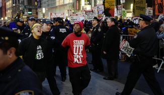 Two men, center, are arrested by police officers after blocking Broadway in front of a McDonald's restaurant, Tuesday, Nov. 29, 2016, in New York. About 25 chanting minimum-wage protesters were arrested. They were among about 350 people at a peaceful rally Tuesday. The event was part of the National Day of Action to Fight for $15. The campaign seeks higher hourly wages, including for workers at fast-food restaurants and airports. (AP Photo/Mark Lennihan)