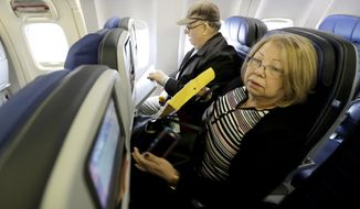 Dania Rivero, right, and her husband Jesus Rivero, of West New York, N.J., settle into their seats on United Flight 1502 the first direct passenger flight from Newark Liberty International Airport to Havana, Cuba, Tuesday, Nov. 29, 2016, in Newark, N.J. Commercial flights between the United States and Cuba resumed several months ago as relations between the two countries gradually improved under President Barack Obama. (AP Photo/Julio Cortez)