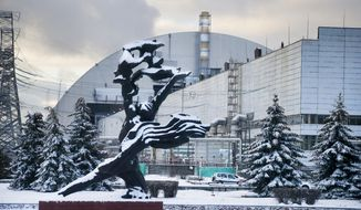 The monument to the victims of the Chernobyl tragedy is in front of a new shelter installed over the exploded reactor at the Chernobyl nuclear plant, Chernobyl, Ukraine, Tuesday, Nov. 29, 2016. A massive shelter has finally been installed over the exploded reactor at the Chernobyl nuclear plant, one of the most ambitious engineering projects in the world. (AP Photo/Efrem Lukatsky)