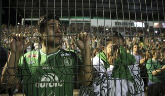 Fans of Brazil's Chapecoense soccer team cry during a tribute to the players who died in a plane crash in Colombia, at Arena Condado stadium in Chapeco, Brazil, Wednesday, Nov. 30, 2016. Authorities were working to finish identifying the bodies before repatriating them to Brazil. (AP Photo/Andre Penner)