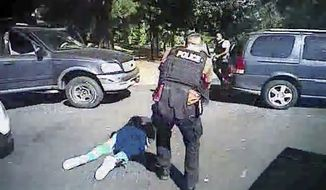 This image made from video provided by the Charlotte-Mecklenburg Police Department on Saturday, Sept. 24, 2016, shows Keith Scott on the ground as police approach him in Charlotte, N.C., on Sept. 20, 2016. Charlotte-Mecklenburg District Attorney Andrew Murray announced Wednesday, Nov. 30, 2016, that the shooting by officer Brent Vinson was justified. Vinson, who is black, shot and killed Keith Lamont Scott on Sept. 20. (Charlotte-Mecklenburg Police Department via AP)