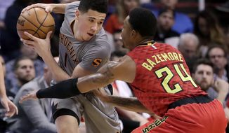 Phoenix Suns guard Devin Booker is defended by Atlanta Hawks forward Kent Bazemore (24) during the first half of an NBA basketball game, Wednesday, Nov. 30, 2016, in Phoenix. (AP Photo/Matt York)