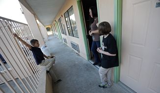 Ashleigh Dickerson and her daughter Christian, 10, talk with temporary neighbor Daron Brose, in the hotel where they are now living, in Denham Springs, La., Wednesday, Nov. 16, 2016. Before the floods came, Ashleigh Dickersons family lived in a three-bedroom house on a private road with plenty of room for her young children to play. (AP Photo/Gerald Herbert)