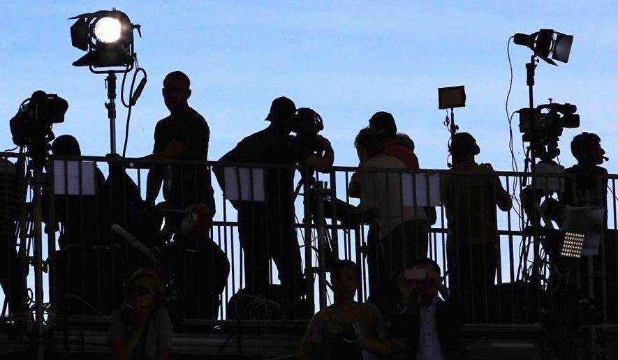 Reporters and photographers on the watch at a press stakeout. (Associated Press)