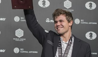 Magnus Carlsen, of Norway, smiles as he holds up his championship trophy during the award ceremony at the World Chess Championship, Wednesday, Nov. 30, 2016, in New York. Reigning champ Carlsen defeated Sergey Karjakin, of Russia. (AP Photo/Mary Altaffer)