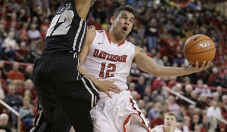 FILE - In this March 5, 2015, file photo, Davidson's Jack Gibbs (12) looks to score against Virginia Commonwealth's Terry Larrier (22) during the second half of an NCAA college basketball game in Davidson, N.C. He may not be Stephen Curry, but another top notch shooter has emerged at Davidson in Jack Gibbs.  (AP Photo/Bob Leverone, File)