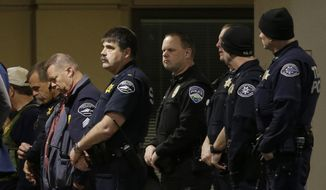 Law enforcement officers gather at Tacoma General Hospital, where a Tacoma Police officer was taken after being shot while responding to a call Wednesday evening, Nov. 30, 2016, in Tacoma, Wash. Authorities say the officer shot multiple times while responding to a domestic violence call has died. Tacoma Police spokeswoman Loretta Cool says the officer was pronounced dead at the hospital Wednesday evening.  (AP Photo/Ted S. Warren)
