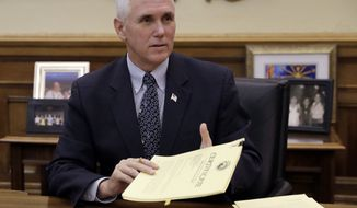 Vice President-elect Mike Pence signs off on paperwork sending Indiana's electors to the electoral college at the Statehouse Friday, Dec. 2, 2016, in Indianapolis. (AP Photo/Darron Cummings)