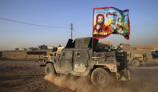 """An Iraqi Special Forces vehicle displays a Shiite flag bearing the likeness of Imam Hussein and Imam Ali with Arabic words reading """"At your service Hussein"""" in Mosul, Iraq. State-sanctioned Shiite militias are positioning themselves to control areas liberated from Islamic State militants in northern Iraq, opening the door to fresh domestic and regional conflict and raising concerns among religious and ethnic minorities. (Associated Press/File)"""
