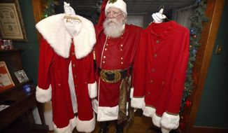 ADVANCE FOR SATURDAY, DEC. 3, AND THEREAFTER - In this Nov. 23, 2016 photo, John Gable, dressed as Santa Claus, holds up two of his other Santa suits while standing in his home in Lebanon, Pa. Gable, who works in customer service and took up his seasonal hobby of portraying Santa Claus in 2005, is such a stickler for detail that he bleaches his brown hair and beard, and learned leatherwork to craft his belt. (Michael K. Dakota/Lebanon Daily News via AP)