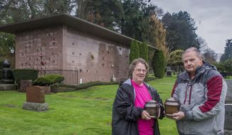In this Nov. 16, 2016 photo, Loretta and Jim Dimond hold metal urns containing the ashes of Civil War veteran James Powers and his wife Irena Powers in Lake View Cemetery in Seattle, Wash. The urns sat unclaimed for decades in the mausoleum (rear) until discovered through a records search by Loretta Dimond of Kent. Her husband Jim Dimond and Bob Patrick of Missing in America Project gathered evidence and won the right for the remains to be intered at Tahoma National Cemtery in Kent in a ceremony in December. (Peter Haley/The News Tribune via AP)