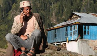 """In this Tuesday Oct. 4, 2016 photo, Jabe Ram speaks on a mobile phone outside his home on the upper end of Malana village in the northern Indian state of Himachal Pradesh. Malana has become one of the world's top stoner destinations, and a symbolical battleground for India's fight against 'charas,' the black and sticky hashish that has made the village famous. """"They want us to completely stop growing marijuana. But we keep sowing it,"""" Ram said. """"If the government helped us in some way and protected us from hunger and cold, we would maybe consider stopping. Obviously, we are not going to go hungry. Even if we have to go to jail for it, so be it."""" (AP Photo/Rishabh R. Jain)"""