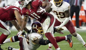 Arizona Cardinals wide receiver Larry Fitzgerald (11) is hit by Washington Redskins defensive end Chris Baker (92) during the second half of an NFL football game, Sunday, Dec. 4, 2016, in Glendale, Ariz. (AP Photo/Rick Scuteri)