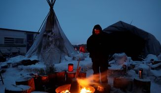 James Logan, a Northern Arapaho Native American from Wyoming and pipeline protester, warms himself by a fire. Activists have vowed to stay in the camps, even after the Obama administration blocked the pipeline, and the chairman of the Standing Rock Sioux tribe has asked non-native protestors to leave. (Associated Press)