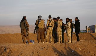 Kurdish peshmerga fighters stand on a sand barrier created by Kurdish forces to demarcate their border, in the Nineveh plain, northeast of Mosul, Iraq.  (AP Photo/Hussein Malla)
