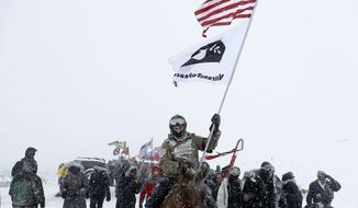 U.S. Navy veteran Kash Jackson rides a horse during a march with fellow veterans and Native Americans to a closed bridge outside the Oceti Sakowin camp where people have gathered to protest the Dakota Access oil pipeline in Cannon Ball, N.D., Monday, Dec. 5, 2016. (AP Photo/David Goldman)
