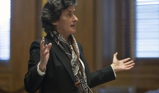 """Assistant Attorney General Loretta Simon, representing the state Department of Environmental Conservation, speaks during a hearing on new snowmobile trails being carved through the Adirondack forest on Monday, Dec. 5, 2016, in Albany, N.Y. A state court will decide whether the new trails violate the """"forever wild"""" clause of New York's constitution. (AP Photo/Mike Groll)"""