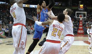 Oklahoma City Thunder guard Russell Westbrook (0) is defended by Atlanta Hawks' Paul Millsap (4), Kent Bazemore (24) and Mike Muscala (31) as he drives to the basket in the first half of an NBA basketball game Monday, Dec. 5, 2016, in Atlanta. (AP Photo/John Bazemore)