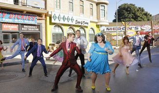 "This image released by NBC shows Derek Hough as Corny Collins, foreground left, and Maddie Baillio as Tracy Turnblad, foreground right, during a rehearsal for the musical ""Hairspray Live!,"" airing on Dec. 7.  Sets for the musical were designed by Broadway set designer Derek McLane. (Trae Patton/NBC via AP)"