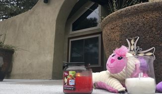 A small memorial of a stuffed animal and candles left by neighbors sits outside an Albuquerque, N.M, home on Tuesday, Dec. 6, 2016, a day after police say a man broke in and fatally shot three children. Albuquerque police say the three children were killed and their mother is in critical condition after the gunman shot them when they arrived home Monday night. Authorities say the gunman was in a short relationship with the mother. (AP Photo/Russell Contreras)