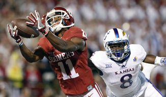 FILE - In this Oct. 29, 2016, file photo, Oklahoma wide receiver Dede Westbrook (11) makes a catch for a touchdown ahead of Kansas cornerback Brandon Stewart (8) during the first half of an NCAA college football game in Norman, Okla. Westbrook was selected Offensive Player of the Year for The AP All Big 12 team, Tuesday, Dec. 6, 2016. (AP Photo/Alonzo Adams, File)