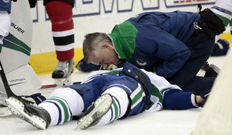 A trainer talks to Vancouver Canucks defenseman Philip Larsen, of Finland, after he was knocked down on a hit by New Jersey Devils left wing Taylor Hall during the second period of an NHL hockey game, Tuesday, Dec. 6, 2016, in Newark, N.J. Larsen left the game on a stretcher. (AP Photo/Julio Cortez)