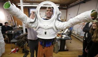 In this Monday, Dec. 5, 2016 photo, Andrzej Stewart, the chief engineering officer on a year-long Mars simulation mission that ended in August, puts on a new space suit at the Rhode Island School of Design (RISD) in Providence, R.I. RISD created the new space suit for scientists to wear on the next Mars simulation mission in 2017 in Hawaii. (AP Photo/Steven Senne)