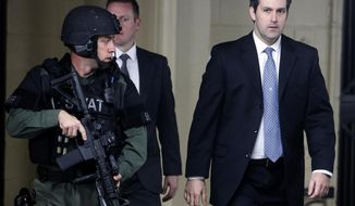 FILE- In this Monday, Dec. 5, 2016 file photo, Michael Slager, at right, walks from the Charleston County Courthouse under the protection from the Charleston County Sheriff's Department after a mistrial was declared for his trial in Charleston, S.C. Relatives of Walter Scott, the black motorist fatally shot while fleeing a traffic stop, say they are confident justice will prevail even though a South Carolina jury could not reach a verdict in the murder trial of a white former police officer charged in his death. (AP Photo/Mic Smith, File)