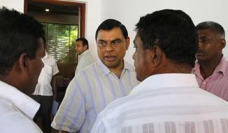 In this Saturday, Dec. 3, 2016, photo, Basil Rajapaksa, center, Sri Lanka's former economic affairs minister and brother of Mahinda Rajapaksa, speaks to supporters at the party office of the newly launched Sri Lanka Podujana Peramuna or Sri Lanka People's Front party in Colombo, Sri Lanka. Although still an official member of Sri Lanka Freedom Party, the goal of the newly launched Sri Lanka Podujana Peramuna party is widely expected to resurrect Rajapaksa's fortunes after he lost the Sri Lankan presidency in 2015 in a stunning electoral upset. (AP Photo/Eranga Jayawardena)