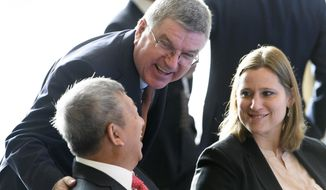 International Olympic Committee, IOC, President Thomas Bach, center, speaks with IOC members Angela Ruggiero, right, of the US and Ser Miang Ng, left, of Singapore at the opening of the first day of the executive board meeting of the IOC, in Lausanne, Switzerland, Tuesday, Dec. 6, 2016. (Laurent Gillieron/Keystone via AP)
