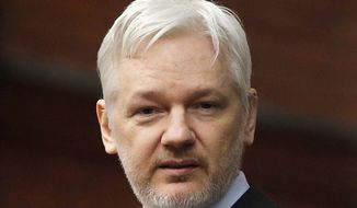 WikiLeaks founder Julian Assange stands on the balcony of the Ecuadorean Embassy in London, Feb. 5, 2016. (AP Photo/Frank Augstein) ** FILE **