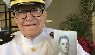 In this Monday, Dec. 5, 2016 photo, Jim Downing, 103, poses in a Navy uniform in Honolulu, with a photo of himself taken when he was about 20 years old. Downing is among a few dozen survivors of the Japanese attack on Pearl Harbor who plan to gather at the Hawaii naval base Wednesday, Dec. 7, 2016, to remember those killed 75 years ago. (AP Photo/Audrey McAvoy)