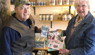 In this Tuesday, Dec. 6, 2016 photo, Charles Robb Sr., left, and Helen Robb pose with their maple syrup at their farm in West Brattleboro, Vt. Their sales have jumped 60 percent since Brooke Shields recommended their syrup in a People Magazine holiday gift guide. (AP Photo/Lisa Rathke)