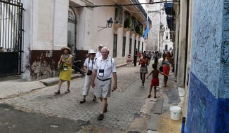 In this May 24, 2015 photo, US tourists walks outside the Bodeguita del Medio Bar frequented by the late American novelist Ernest Hemingway in Old Havana, Cuba. One airline's cutback in flights to Cuba may be a sign that demand for travel to the island is slowing down amid uncertainty about Donald Trump's Cuba policies along with a near-doubling of Havana hotel prices and concerns over Zika. (AP Photo/Desmond Boylan, File)